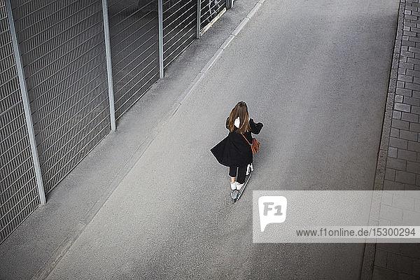 Rückansicht eines jugendlichen Mädchens auf einem Elektroroller auf der Straße in der Stadt Rückansicht eines jugendlichen Mädchens auf einem Elektroroller auf der Straße in der Stadt
