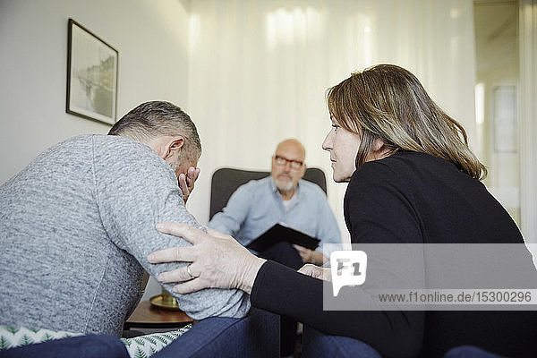 Woman consoling man during counseling session with therapist