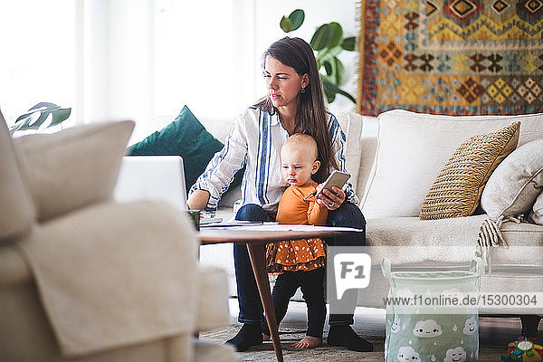 Multi-tasking mother using laptop while taking care of daughter in living room