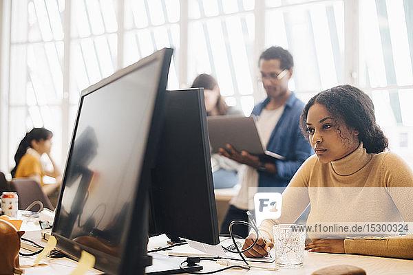 Fokussierte Geschäftsfrau  die einen Computer benutzt  während ihre Kollegen im Hintergrund im Büro arbeiten