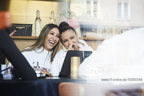 Happy female teenage friends sitting at table in restaurant