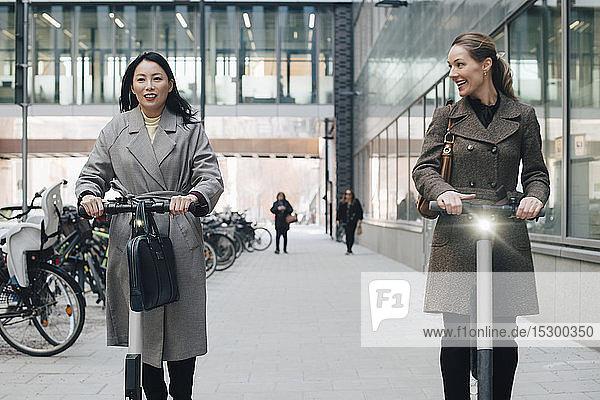 Lächelnde Kolleginnen auf Elektro-Schieberoller auf einem Fußweg durch ein Gebäude in der Stadt Lächelnde Kolleginnen auf Elektro-Schieberoller auf einem Fußweg durch ein Gebäude in der Stadt