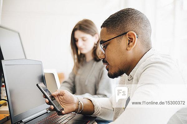 Männlicher Computerprogrammierer benutzt ein Smartphone  während er neben einer Kollegin am Schreibtisch im Büro sitzt