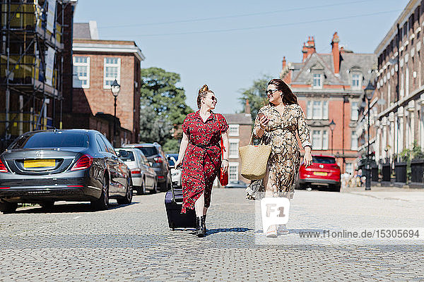 Two friends walking on the street with wheeled luggage and shopping bag looking at each other  Liverpool  UK