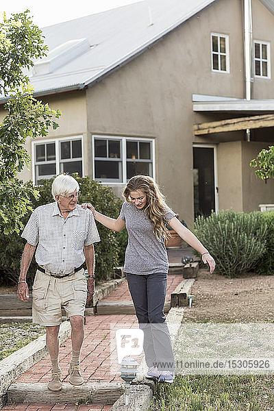 Eine junge Teenagerin und ihr Großvater gehen gemeinsam einen Weg.
