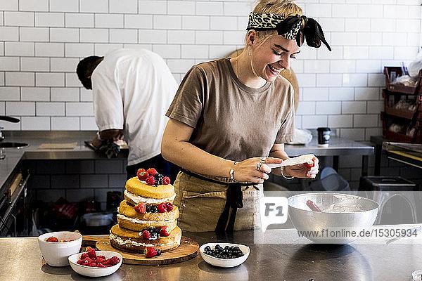 Ein Koch  der in einer Großküche arbeitet und einen Biskuitkuchen mit frischen Früchten zusammensetzt.