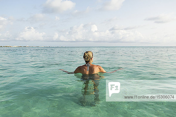 Adult woman standing in ocean water at sunset