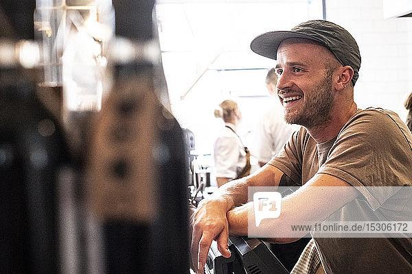 Porträt eines bärtigen Mannes mit Baseballmütze  der lächelnd in einem Cafe steht.