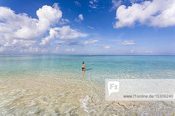 Ein junges Mädchen steht im Meer