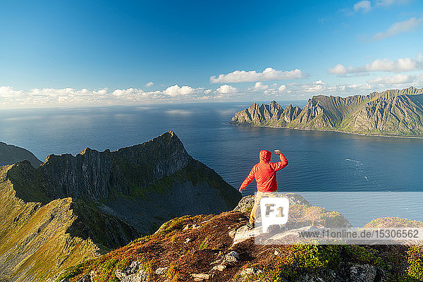 Man with arms spread in celebration on top of mountain  Senja Island  Troms