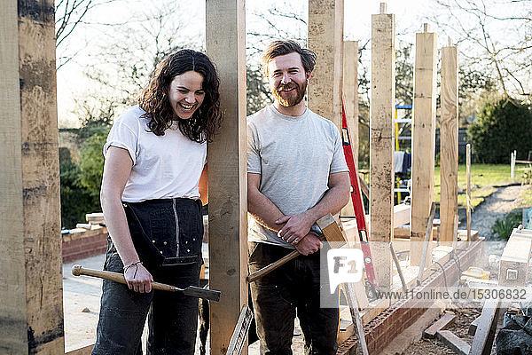 Lächelnder Mann und Frauen mit Handwerkzeugen in der Hand stehen auf der Baustelle eines Wohnhauses.