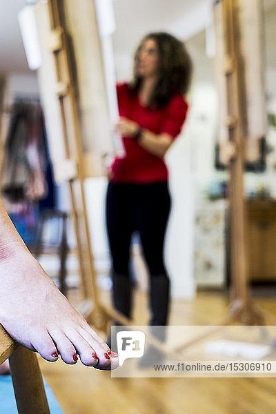Nahaufnahme eines nackten weiblichen Fußes mit rot lackierten Zehennägeln  ein Modell in einem Zeichenkurs an der Kunstschule. Im Hintergrund arbeitet ein Künstler.