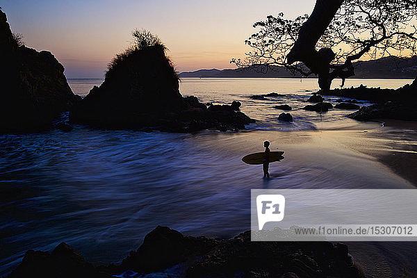 Silhouette boy with surfboard on ocean beach  Sayulita  Nayarit  Mexico