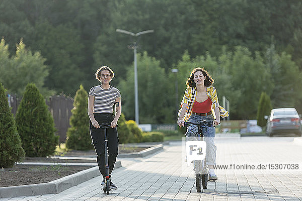 Freundinnen fahren Fahrrad und schieben Roller auf der Straße