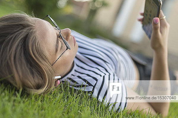 Young woman using smart phone in grass