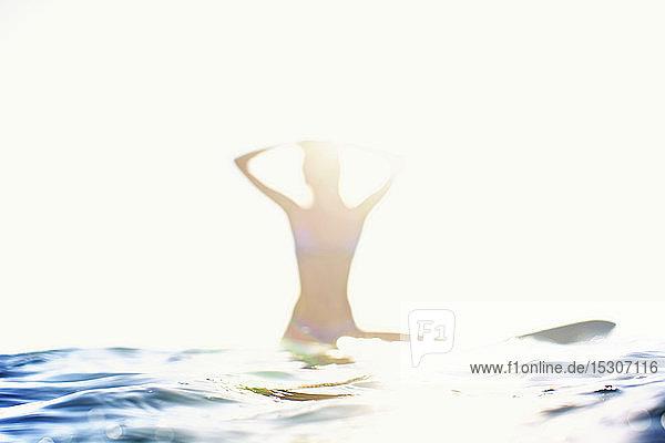 Female surfer sitting on surfboard on sunny ocean