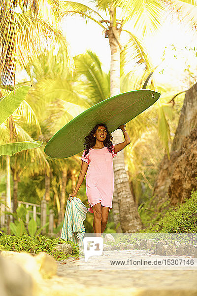 Female surfer carrying surfboard overhead below sunny palm trees
