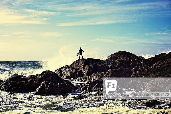 Silhouette male surfer watching ocean waves crash against rocks on sunny beach  Tofino  Canada