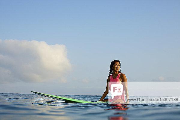 Female surfer waiting on surfboard in ocean