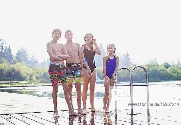 Portrait tween friends in bathing suits standing on sunny lake dock