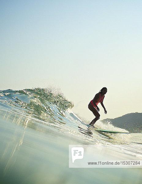 Female surfer riding ocean wave