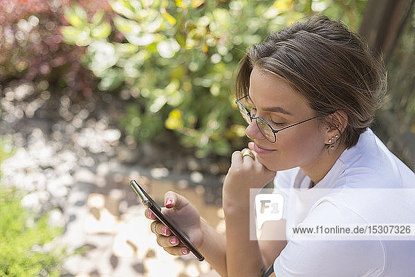 Young woman using smart phone in park