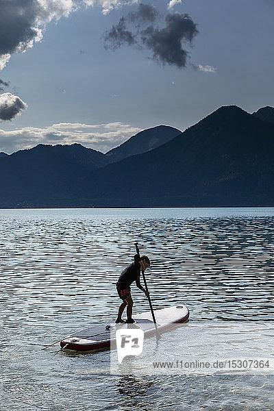 Junge beim Paddeln auf einem sonnigen  idyllischen See  Walchensee  Bayern  Deutschland