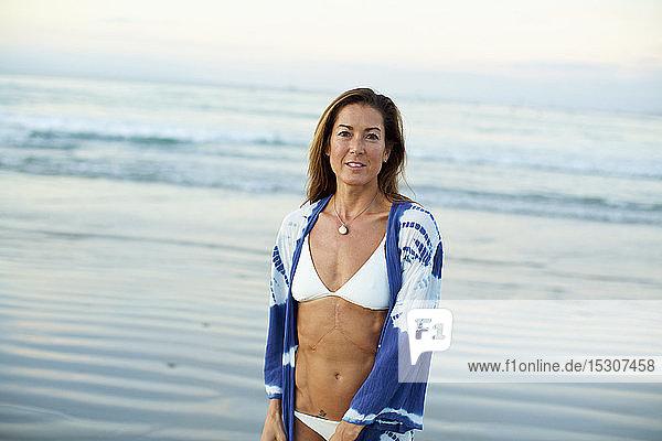 Portrait confident woman in bikini on ocean beach