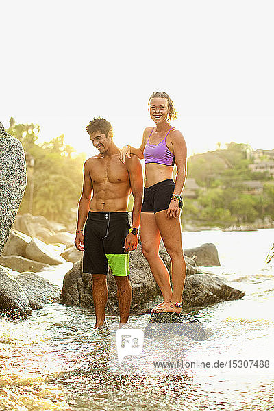 Young  fit couple standing on ocean rocks  Sayulita  Nayarit  Mexico