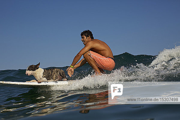 Young man and dog riding surfboard on ocean wave
