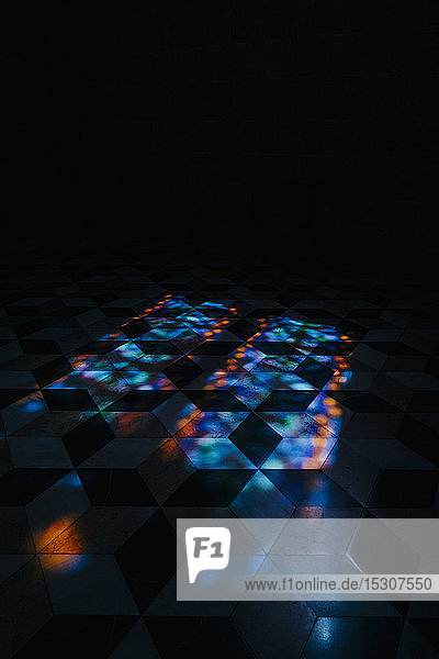 Kaleidoscope reflection of lights on tile floor