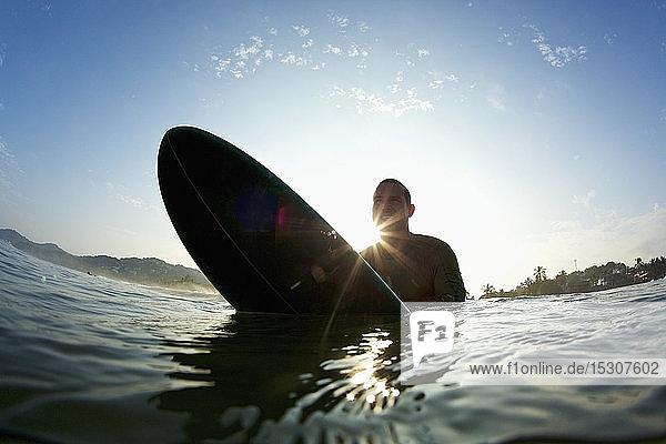 Silhouette male surfer straddling surfboard in sunny ocean