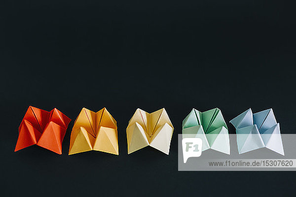 Rainbow multicolored origami fortune tellers on black background