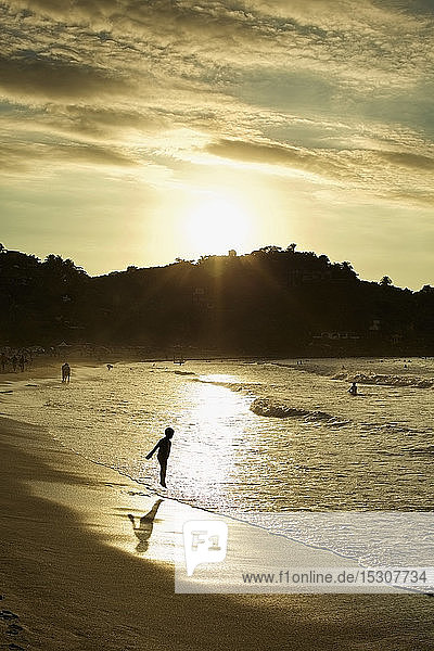 Silhouette boy wading in ocean surf on tranquil beach at sunset  Sayulita  Nayarit  Mexico