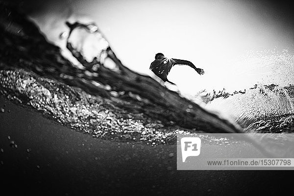 Male surfer making cutback from behind ocean wave