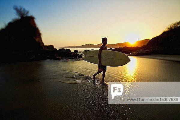 Silhouette boy with surfboard walking on idyllic ocean beach  Sayulita  Nayarit  Mexico