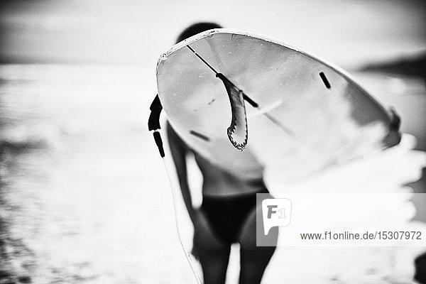 Female surfer carrying surfboard on ocean beach