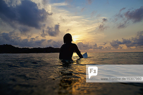 Silhouette surfer sitting on surfboard in tranquil ocean at sunset  Sayulita  Nayarit  Mexico