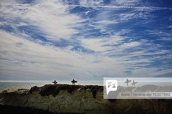 Surfers carrying surfboards on ocean rocks  Santa Cruz  California  USA