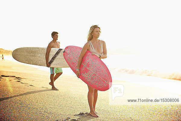 Young couple with surfboards walking on sunny beach