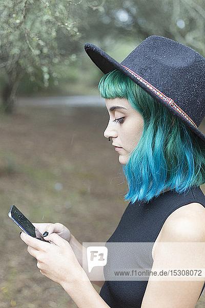 Profil einer jungen Frau mit blau und grün gefärbten Haaren  die an einem regnerischen Tag ein Smartphone benutzt
