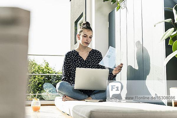 Junge Frau zu Hause mit Laptop und durchsichtigem Dokument