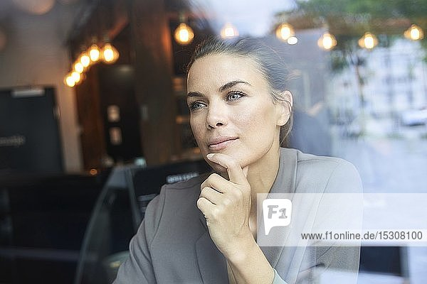 Portrait of thoughtful businesswoman behind windowpane in a cafe