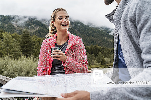 Young woman with drink smiling at man during a hiking trip  Vorderriss  Bavaria  Germany
