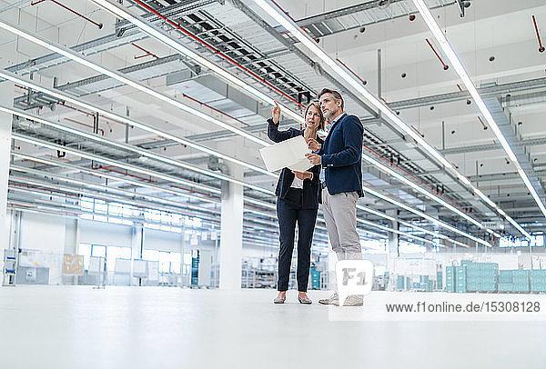 Geschäftsmann und Geschäftsfrau besprechen Plan in einer Fabrikhalle
