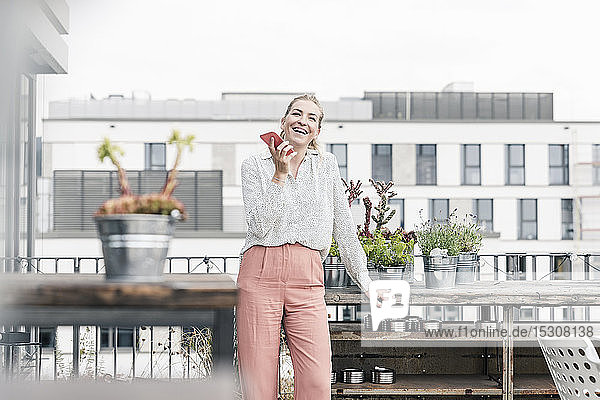 Happy casual businesswoman using cell phone on roof terrace