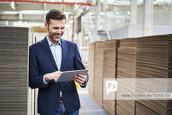 Lächelnder Geschäftsmann mit Tablette im Fabriklager