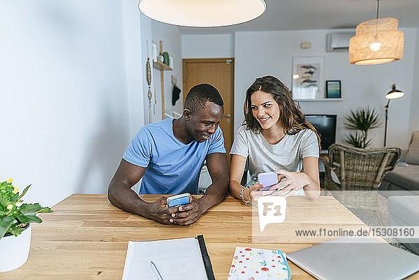 Glückliches Paar benutzt zu Hause sein Handy