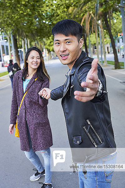 Happy couple inviting someone to join them for a walk  Barcelona  Spain