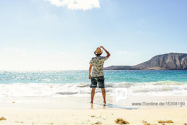 Rear view of man with hat at Playa de las Conchas  Lanzarote  Canary Islands  Spain